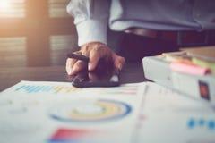 De zakenlieden richten hun vinger op financiële grafieken om het bedrijf ` s voorbij prestaties aan te tonen royalty-vrije stock afbeeldingen