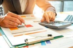 De zakenman analyseert grafiekgegevens en gebruikt de calculator aan calcul Stock Foto