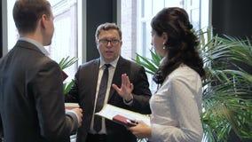 De zakenman beantwoordt de vragen van zijn collega in de gang tijdens de conferentie stock videobeelden