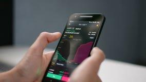 De zakenman bekijkt Bitcoin-prijs deapth grafiek op digitale uitwisseling op het mobiele telefoonscherm, cryptocurrencytoekomst stock videobeelden