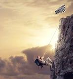 De zakenman beklimt een berg om de vlag te krijgen Voltooiings bedrijfsdoel en Moeilijk carrièreconcept stock foto