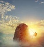 De zakenman beklimt een berg om de vlag te krijgen Voltooiings bedrijfsdoel en Moeilijk carrièreconcept stock foto's