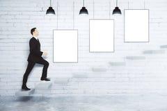 De zakenman beklimt op de treden bij witte bakstenen muur met spatie stock afbeeldingen