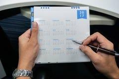 De zakenman belegt vergadering over de kalender van 2017 in handen Stock Foto's