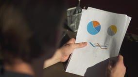 De zakenman bestudeert grafiek en maakt geplande aanpassingen voor de toekomstige holdingsrapporten met grafiekenclose-up stock videobeelden
