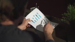 De zakenman bestudeert de rapporten van de grafiekholding met grafiekenclose-up Financiële bedrijfsgrafiek met diagrammen stock video