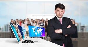 De zakenman bevindt zich dichtbij laptop met de vele schermen royalty-vrije stock afbeeldingen