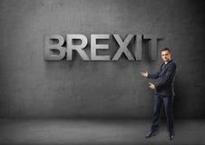 De zakenman bevindt zich tonend grote 3d & x27; brexit& x27; woord door beide handen op concrete achtergrond Stock Foto's