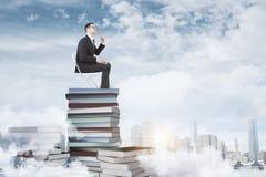 De zakenman, de boeken en de stoel van het onderwijsconcept Stock Foto's
