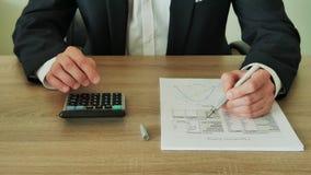 De zakenman controleert de berekeningen op een calculator in het bureau van houten lijst 4K stock footage