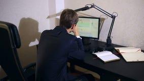 De zakenman controleert veranderingen in het programma op de muntuitwisseling, bekijkend de computermonitor stock videobeelden