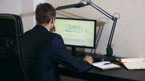 De zakenman controleert veranderingen in het programma op de muntuitwisseling, bekijkend de computermonitor stock video