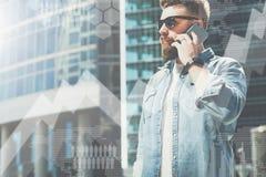 De zakenman in denimoverhemd bevindt zich op stadsstraat en spreekt op zijn celtelefoon In voorgrond virtuele grafiek, grafieken stock fotografie