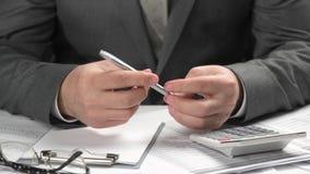 De zakenman denkt over te schrijven wat Hij die en het berekenen financiën werken bedrijfs financi?le boekhoudingsconcept close-u stock video