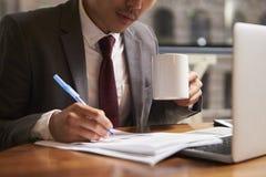 De zakenman die aan de koffiemok van de documentholding werken, sluit omhoog royalty-vrije stock foto's