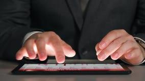 De zakenman die aan een tablet werken, analyseert de grafieken en de lijsten, overhandigt close-up stock footage