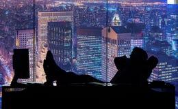 De zakenman die in donkere ruimte bij wolkenkrabber werken Royalty-vrije Stock Afbeeldingen