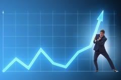 De zakenman die de economische groei in bedrijfsconcept proberen te helpen stock foto's