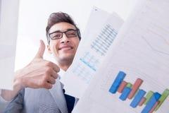 De zakenman die financiële grafieken en grafieken bekijken stock foto's