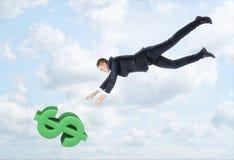 De zakenman die neer aan het grote dollarteken vliegen met zijn handen outstreched op de achtergrond van de blauwe hemel Royalty-vrije Stock Foto's
