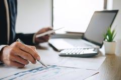 De zakenman die nieuw project op laptop computer met rapportdocument werken en analyseert, berekenend financiële gegevens over gr stock afbeelding