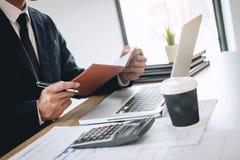 De zakenman die nieuw project op laptop computer met rapportdocument werken en analyseert, berekenend financi?le gegevens over gr stock foto's