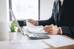 De zakenman die nieuw project op laptop computer met rapportdocument werken en analyseert, berekenend financi?le gegevens over gr royalty-vrije stock foto's
