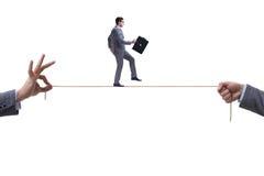 De zakenman die op strakke kabel in bedrijfsconcept lopen stock fotografie