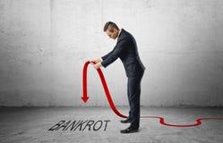 De zakenman die rode lijngrafiek houden met downturned pijl die aan het woord & x27 richt; bankrot& x27; stock foto's
