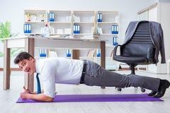 De zakenman die sporten doen bij zijn bureauruimte stock fotografie