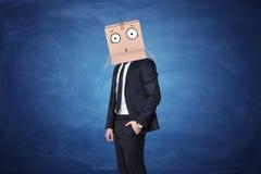 De zakenman draagt kartondoos op zijn hoofd met een getrokken verrast gezicht royalty-vrije stock foto