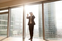 De zakenman draagt vr hoofdtelefoon, richtend vinger in de lucht Stock Foto's