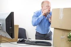 De zakenman drinkt alcohol op het kantoor Stock Afbeeldingen
