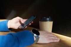 De zakenman drinkt koffie in een koffie, houdt het close-up een beschikbaar document glas, gebruikend smartphone terwijl het hebb royalty-vrije stock foto