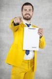 De zakenman in een gouden kostuum toont op u, de nieuwe overeenkomst stock afbeelding