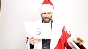 De zakenman in een kostuum van Santa Claus houdt een blad van document met aantallen Definitieve Aftelprocedure stock video