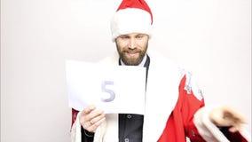De zakenman in een kostuum van Santa Claus houdt een blad van document met aantallen Definitieve Aftelprocedure stock footage
