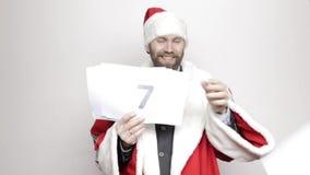 De zakenman in een kostuum van Santa Claus houdt een blad van document met aantallen Definitieve Aftelprocedure stock videobeelden