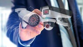 De zakenman een systeem van de Veiligheidscamera houden en het netwerk die verbinden Royalty-vrije Stock Foto