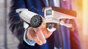 De zakenman een systeem van de Veiligheidscamera houden en het netwerk die verbinden Stock Foto