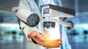 De zakenman een systeem van de Veiligheidscamera houden en het netwerk die verbinden Stock Fotografie
