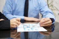 De zakenman en de onderneemster analyseren rapport met hoogtepunt van royalty-vrije stock afbeelding