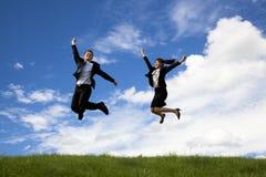 De zakenman en de onderneemster springen Stock Foto's