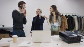 De zakenman en zijn vrouwelijke partners maken heel wat over hun mobiele telefoons en zijn gelukkig over het stock footage
