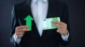 De zakenman euro bankbiljet tonen en de groene pijl die ondertekenen, munt het groeien, inkomen stock videobeelden
