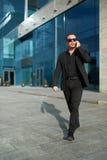 De zakenman gaat en spreekt op telefoon Royalty-vrije Stock Afbeeldingen