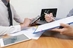 De zakenman gebruikt een calculator om de aantallen te berekenen royalty-vrije stock afbeelding