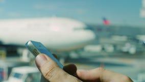 De zakenman gebruikt smartphone bij de luchthaven Handen van een mens met de telefoon op de achtergrond van het vliegveld en stock video