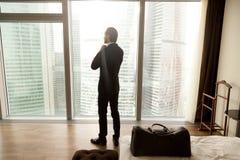 De zakenman geniet van mening van venster in hotelruimte royalty-vrije stock foto