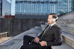 De zakenman geniet van muziek in een onderbreking stock foto
